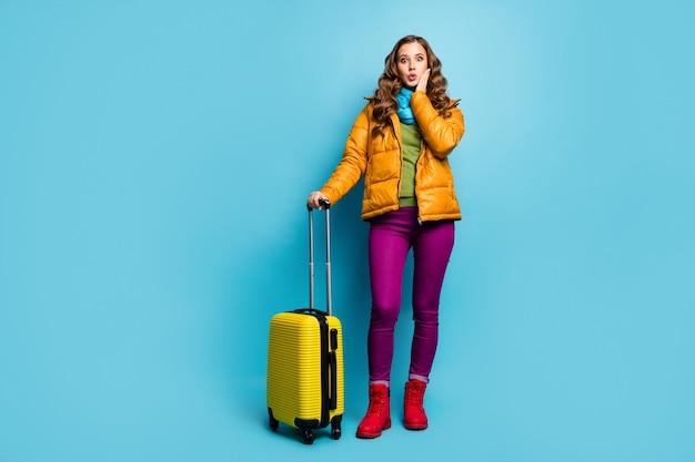 Foto di tutto il corpo della bella signora viaggiatore tenere la borsa da viaggio attendere la registrazione del volo dell'aeroporto lunga coda grande indossare cappotto giallo sciarpa blu pantaloni scarpe isolato muro di colore blu