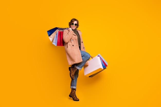 Foto di tutto il corpo di una bella signora che cammina nel centro commerciale porta molti pacchetti addicted shopper indossare specifiche casual cappotto rosa pullover jeans scarpe leopardate