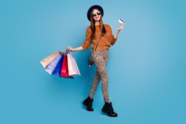 Foto di tutto il corpo della ragazza cliente boutique positiva goditi i fine settimana dello shopping fuori vendita tenere borse occasioni tenere facile pagamento carta di credito indossare pantaloni marroni cappello retrò isolato muro di colore blu