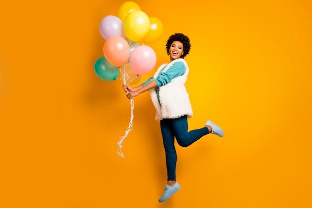 Foto di tutto il corpo emozioni positive ragazza afro-americana hipster salta attesa baloons anniversario indossare bianco elegante maglione verde acqua alla moda pantaloni blu pantaloni scarpe isolato muro di colore brillante
