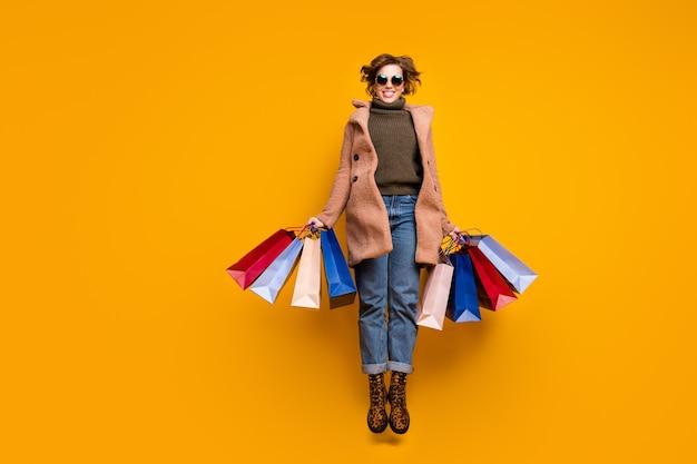Foto di tutto il corpo di una signora piuttosto divertente che salta in alto nel centro commerciale confezioni da attesa indossare occhiali da sole casual cappotto rosa pullover jeans scarpe con stampa leopardata