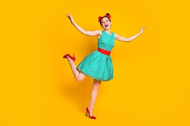 Foto a corpo intero di una bella ragazza che alza le mani indossa abiti verde acqua isolati su uno sfondo di colore brillante