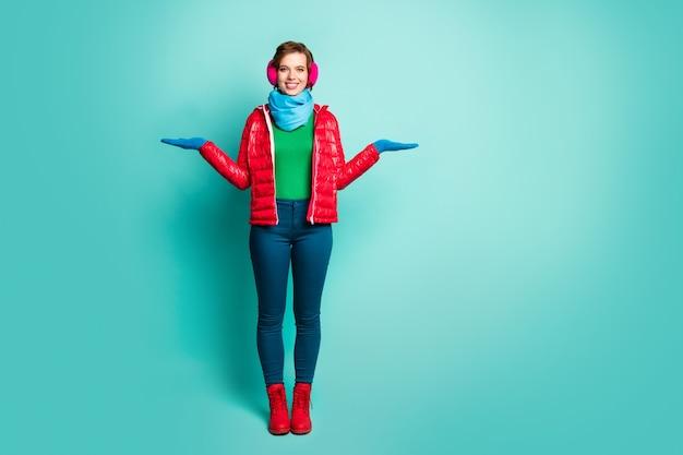 Foto di tutto il corpo di una bella signora tenere due braccia proponendo prodotti di novità indossare casual cappotto rosso sciarpa blu copri orecchie rosa pantaloni jumper scarpe isolato muro color verde acqua