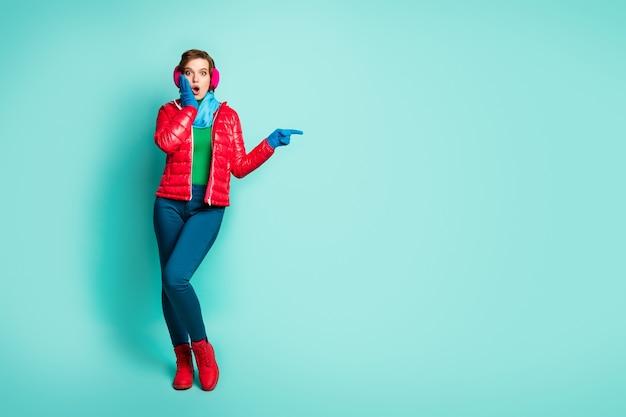 La foto di tutto il corpo della bella signora indica le dita spazio vuoto che mostra i prezzi di vendita mano sulla guancia indossare soprabito rosso sciarpa blu paraorecchie rosa pantaloni scarpe isolato muro color verde acqua