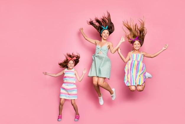 Foto di tutto il corpo di dolci sorelle più giovani che alzano le mani saltando indossando fasce per abiti da sciatore isolate su sfondo rosa