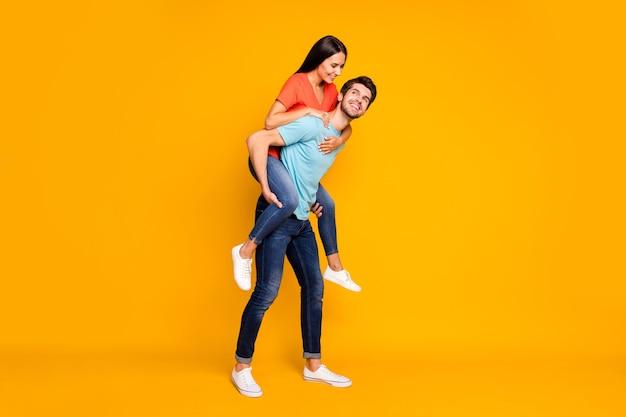 Foto di tutto il corpo di due persone divertenti ragazzo che trasportano lady piggyback incontrare avventure estive insieme indossare casual trendy blu arancione t-shirt jeans isolato muro di colore giallo
