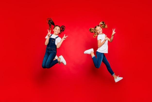 Foto di tutto il corpo di due ragazze dei bambini capelli castani biondi positivi con code aspettano vacanze di natale saltare fare segni v indossare t-shirt casual moderna isolata sopra priorità bassa di colore rosso