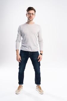 Quadro completo del corpo di un uomo casual sorridente in piedi su sfondo bianco
