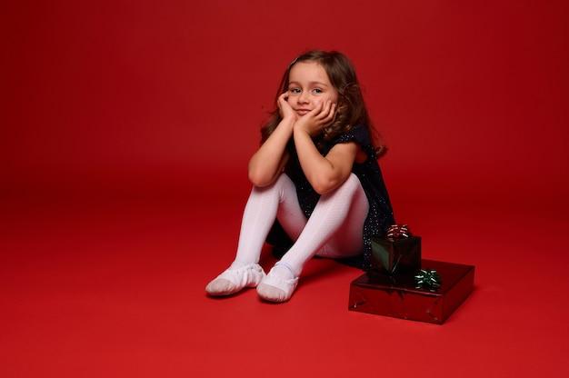 Ritratto completo del corpo di adorabile graziosa bambina di 4 anni in un bellissimo vestito seduto su sfondo rosso accanto alla confezione regalo di natale in carta regalo lucida con fiocco verde glitterato. copia spazio per l'annuncio