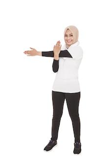 Ritratto completo del corpo della donna sportiva musulmana che fa allungamento della mano