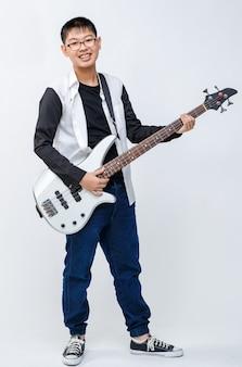 Colpo di ritratto completo del corpo di un adolescente sorridente sveglio del ragazzo che tiene il basso elettrico. il bassista professionista junior in piedi e suona uno strumento mentre guarda lo sfondo bianco isolato della telecamera