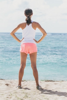 Ritratto completo del corpo di donna sportiva in fase di riscaldamento prima dell'allenamento mentre si affaccia sul mare