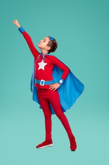 Ragazzo potente di tutto il corpo in costume da supereroe che stringe il pugno e si prepara a volare contro il turchese