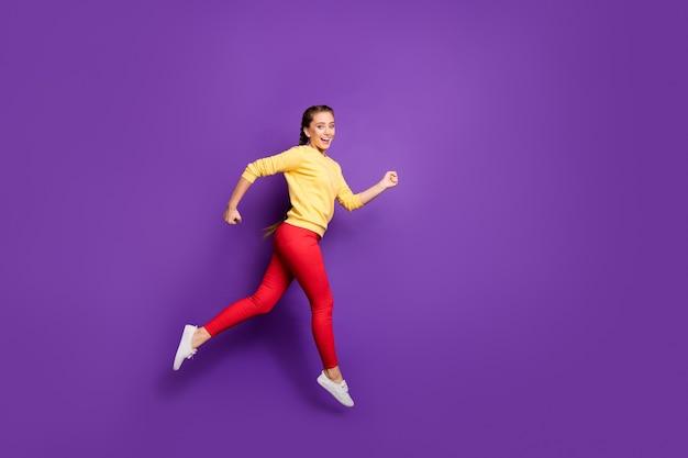Profilo completo del corpo signora millenaria che salta alta corsa veloce vendita shopping velocità corsa abbigliamento da corsa casual giallo pullover pantaloni rossi isolato muro di colore viola