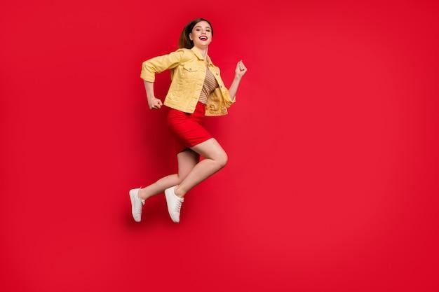 Foto del profilo completo del corpo di una donna attraente di buon umore che salta in alto correndo shopping vendite indossare casual giacca sportiva gialla giacca gonna corta scarpe da ginnastica isolate sfondo di colore rosso vivo