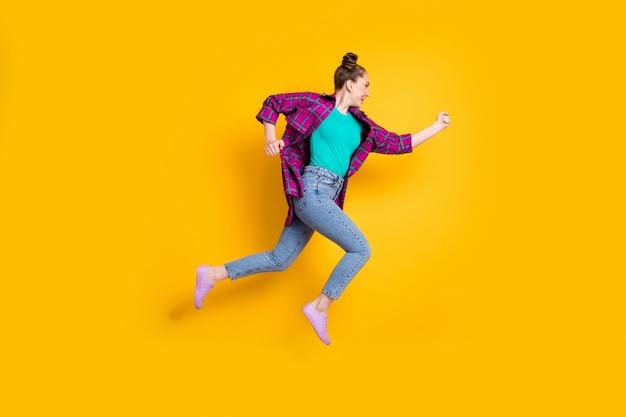 Foto del profilo completo del corpo di una giovane donna attraente che salta in alto corri maratona di corsa entusiasta di vincere la competizione veloce indossare casual camicia a quadri scarpe da ginnastica jeans isolato sfondo di colore giallo