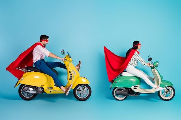 Foto del profilo di tutto il corpo di un ragazzo pazzo che guida due ciclomotori retrò freni a grande velocità smette di indossare la maschera del mantello rosso che gioca a festa super eroi cappotto di ruolo volare aria isolato muro di colore blu