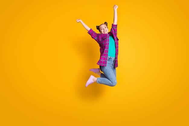 Foto di profilo completo del corpo di una pazza ragazza adolescente che salta in alto campione di volo aereo competizione sportiva felice di indossare casual camicia a quadri scarpe scarpe da ginnastica jeans isolato sfondo di colore giallo