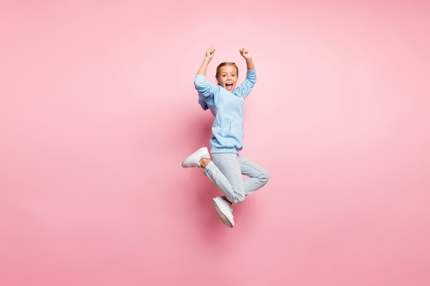 Foto di profilo completo del corpo di una signora piuttosto piccola che salta in alto che celebra la vittoria della migliore competizione sportiva indossare abbigliamento casual isolato sfondo di colore rosa pastello