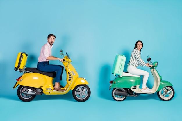 Foto di profilo completo del corpo di ragazzo scioccato signora guidare due retro ciclomotore ora di punta valigie di rotolamento fissate dietro i viaggiatori dipendenti vestiti di abbigliamento formale isolato muro di colore blu
