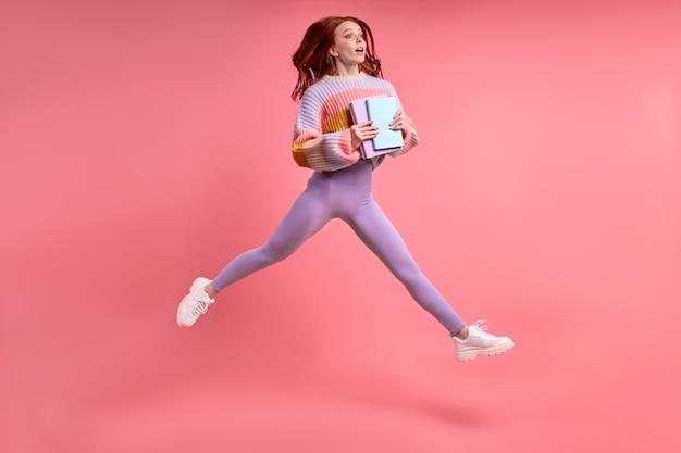 Foto di profilo completo del corpo di una giovane studentessa caucasica dai capelli rossi che salta in alto tenendo il taccuino in mano...
