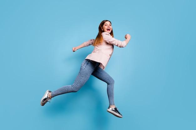 La ragazza allegra laterale del profilo completo del corpo salta corri veloce