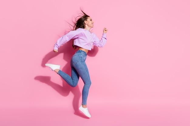 La foto laterale del profilo completo del corpo di una ragazza attiva allegra salta correndo dopo le occasioni di vendita della stagione indossa un pullover elegante e alla moda con scarpe da ginnastica isolato su uno sfondo di colore pastello