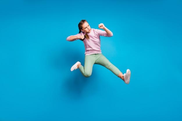 Foto laterale di profilo completo del corpo della ragazza giovanile funky concentrata salto treno le sue abilità di combattimento calcio gamba nemico indossare maglione vestiti moderni isolato su sfondo di colore blu