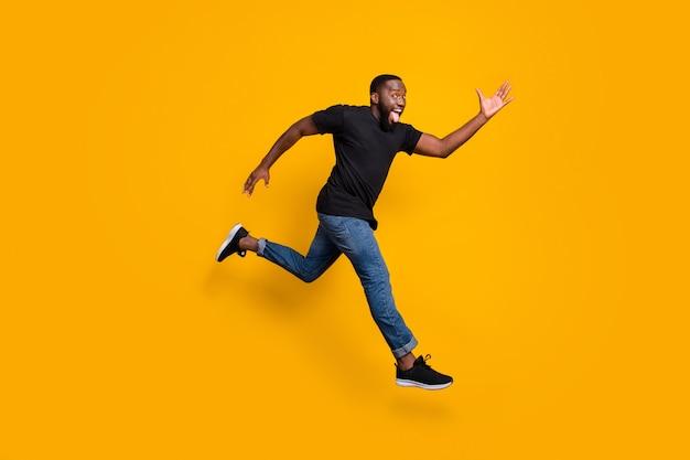 Foto laterale di profilo completo del corpo del ragazzo afroamericano pazzo funky che salta veloce dopo che gli affari indossano abiti alla moda isolati su un muro di colori vivaci