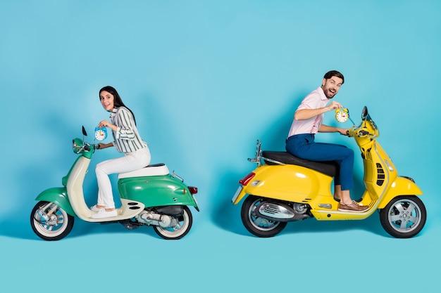 Foto laterale di profilo completo del corpo divertente funky moglie marito coppia unità moto bici goditi il percorso ad alta velocità avventura controlla il tempo sulla campana dell'orologio indossare pantaloni camicia isolata parete di colore blu
