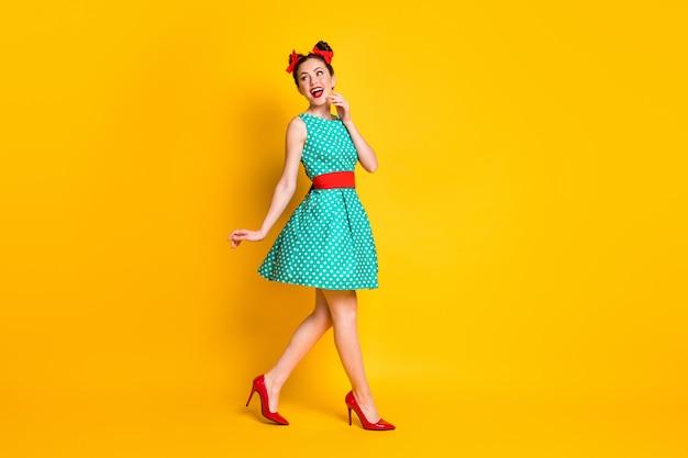 Foto a lato del profilo completo del corpo di una ragazza adorabile che cammina copyspace indossa una gonna isolata brillante sfondo di colore brillante