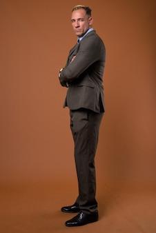 Colpo di corpo pieno di uomo d'affari in piedi sul marrone