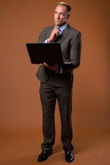 Colpo di corpo pieno di uomo d'affari utilizzando il computer portatile