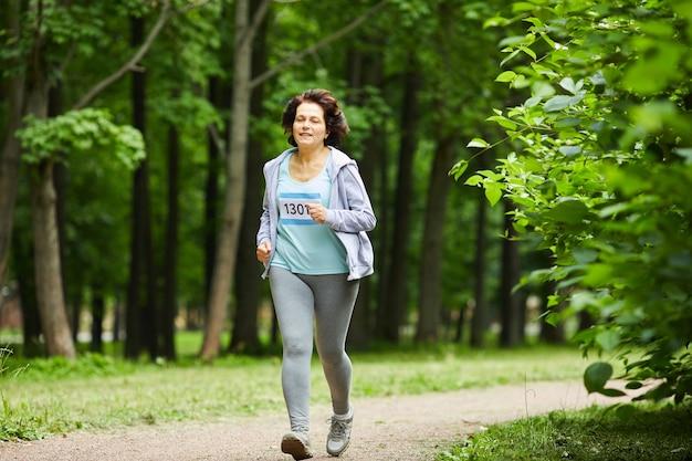 Colpo di corpo pieno di donna matura moderna con capelli castani in esecuzione gara di maratona nel parco forestale
