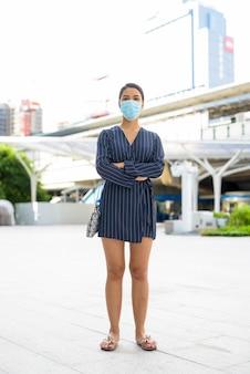 Colpo di tutto il corpo di giovane donna d'affari asiatica che indossa la maschera per la protezione dallo scoppio del virus corona in città