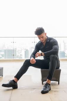 Colpo di corpo pieno di giovane uomo d'affari persiano barbuto che controlla il tempo mentre era seduto