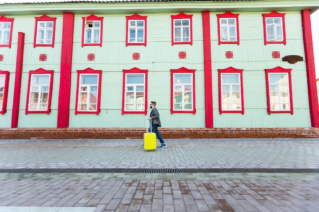 Ritratto completo del lato del corpo dell'uomo di viaggio felice con la valigia che cammina lungo l'edificio in città