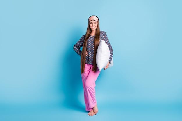 Foto a grandezza naturale di bella ragazza adolescente carina sorridente mano anca tenere cuscino a piedi nudi pronto ad andare a letto indossare maschera camicia punteggiata pigiama pigiameria isolato sfondo di colore blu brillante