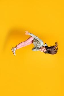 Foto verticale di tutto il corpo di un bellissimo bambino che cade paura braccio guancia bocca aperta felpa con cappuccio stile isolato su sfondo di colore giallo