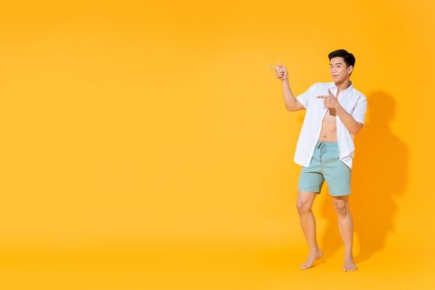 Ente completo di giovane uomo asiatico bello in attrezzatura casuale di estate che indica le mani per copiare lo spazio da parte sulla parete gialla colourful