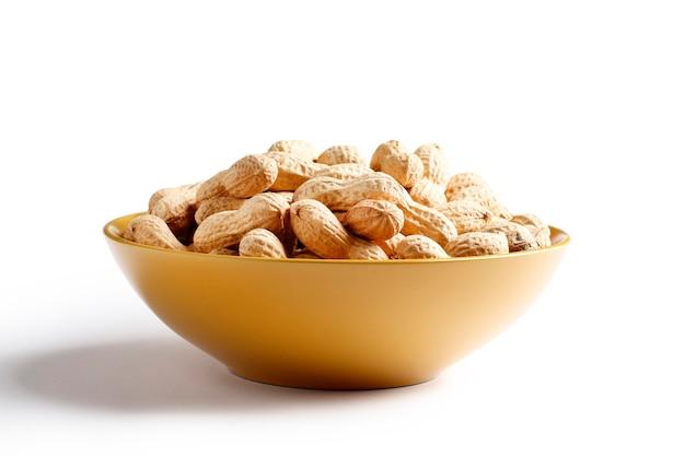 Ciotola piena di arachidi in guscio isolato su sfondo bianco. posto per il testo. vista dall'alto.