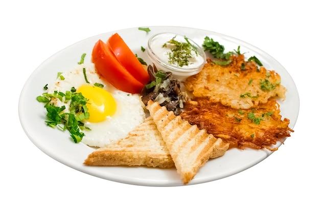 Colazione completa su sfondo bianco uova fritte funghi fritti hash browns frittelle di patate