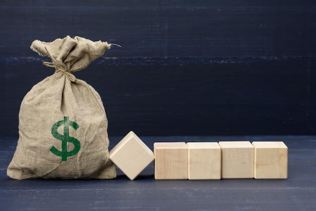 Borsa in tela marrone piena con l'icona del dollaro usa e cinque cubi vuoti in legno su superficie blu