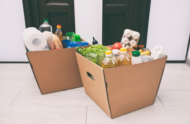 La scatola ecologica piena di cartone con i prodotti del negozio di alimentari sul pavimento di casa vicino alla porta