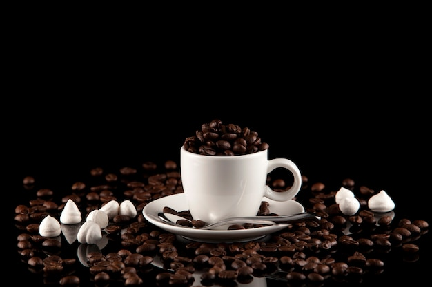 Tazza piena di chicchi di caffè su oscurità