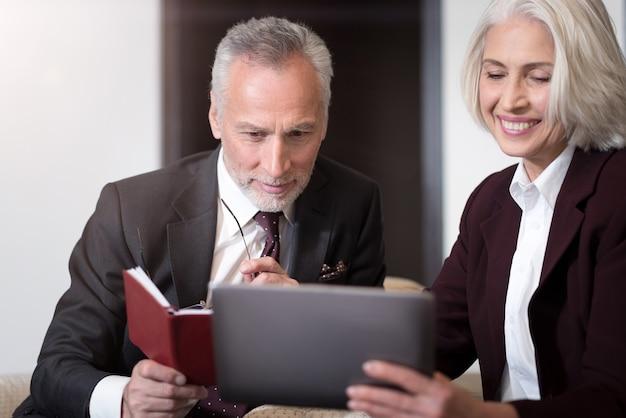 Pieno di gioia. uomo d'affari piacevole allegro positivo che sorride e che si siede nell'ufficio vicino alla donna di affari mentre lavora con il suo collega e che tiene il taccuino