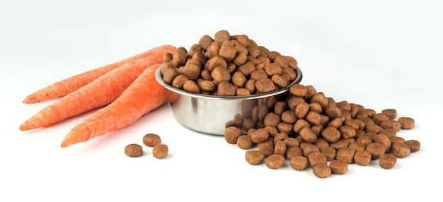 Cibo completo per cani o gatti su piatto inossidabile e carota su bianco