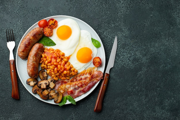Prima colazione inglese completa su un piatto con uova fritte