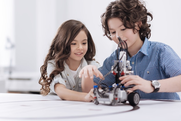 Pieno di entusiasmo. bambini simpatici e attenti che siedono a scuola e creano robot mentre esprimono gioia
