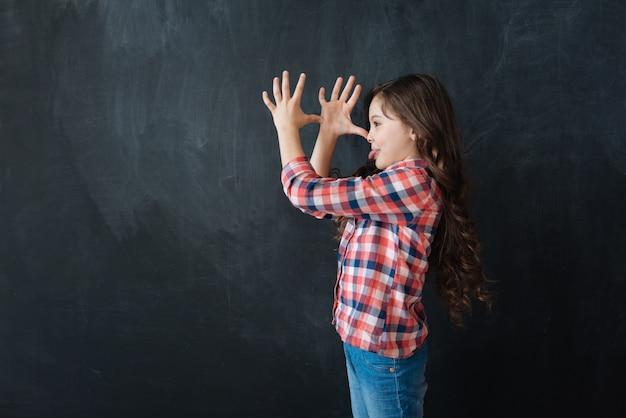 Pieno di espressione. attiva ragazza gioiosa vivace in piedi nella lavagna e suonare la scimmia mentre esprime gioia